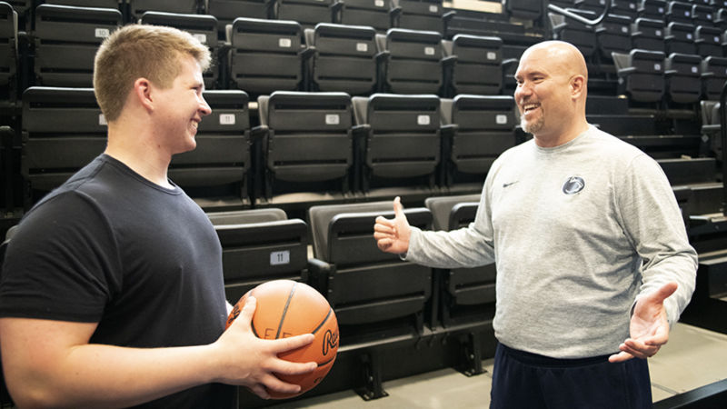 Joshua Crayton (left) and Lou Zadecky, athletic director (right) catch up off the court.