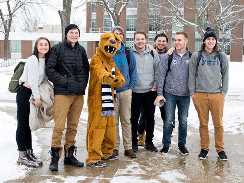 Lion standing with students in the snow.