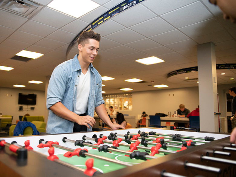 Student playing fuzzball in the Student Center.