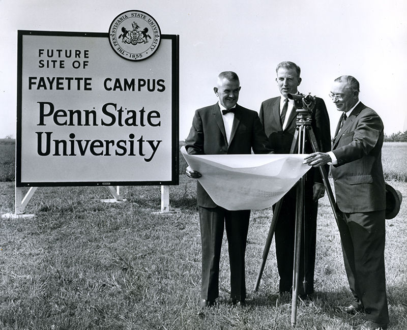 Future site of campus sign with three people.