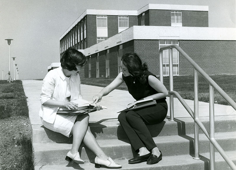 Two students on the steps leading to the Eberly Building.