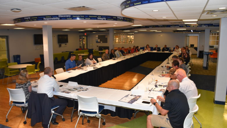 A forum of high school administrators and Penn State Fayette staff are seated around a large table in the Student Center.